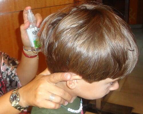 Γυναίκα ψεκάζει τα μαλλιά αγοριού