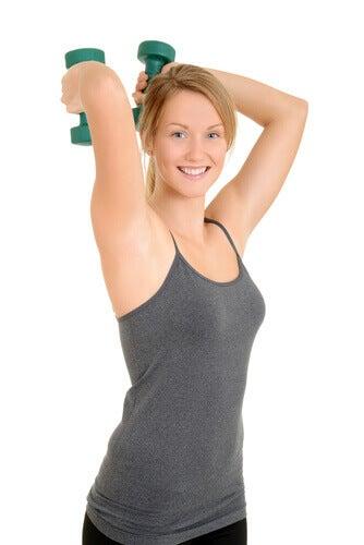 Αντιμετώπιση των πλαδαρών μπράτσων - Γυναίκα κάνει ασκήσεις με αλτήρες