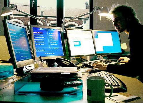 Άνδρας εργάζεται μπροστά σε τρεις οθόνες υπολογιστή