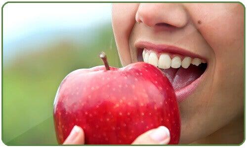 μείωση του λίπους στην κοιλιά- γυναίκα τρώει μήλο