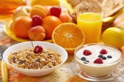 Τονώστε τον μεταβολισμό σας - Φρούτα, βρώμη και γιαούρτι σε μπολ, φυσικό χυμός σε ποτήρι