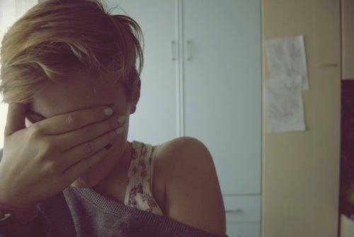 Γυναίκα καλύπτει το πρόσωπό της με το χέρι της