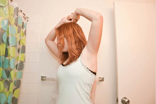 Γυναίκα ελέγχει τη μασχάλη της στο μπάνιο