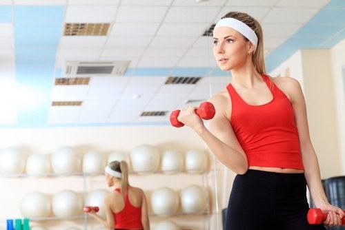 Σφιχτό στήθος - Γυναίκα κάνει ασκήσεις με αλτήρες