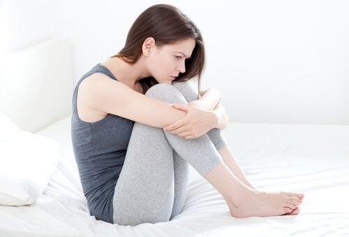 Αιμορραγία ανάμεσα στις περιόδους - Γυναίκα κάθεται στο κρεβάτι