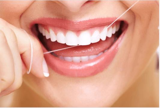 Θεραπείες αντιμετώπισης του πονόδοντου - Γυναίκα καθαρίζει τα δόντια της με οδοντικό νήμα
