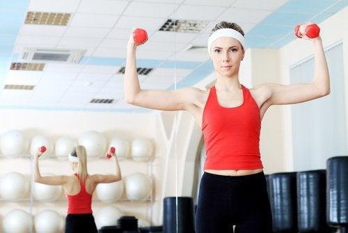 Αντιμετώπιση χαλάρωσης του στήθους - Γυναίκα γυμνάζεται με αλτήρες