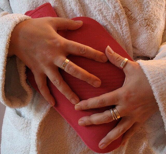 Προβλήματα με τον θυρεοειδή - Γυναίκα με θερμοφόρα στο στομάχι
