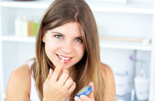 Καλλυντικές χρήσεις της βαζελίνης - Γυναίκα εφαρμόζει βαζελίνη στα χείλη