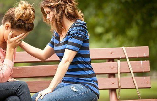 Δύο κοπέλες κάθονται σε παγκάκι