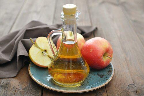 Αφαιρέστε τις κρεατοελιές με φυσικό τρόπο - Μηλόξυδο σε δοχείο και κομμένα μήλα σε πιάτο