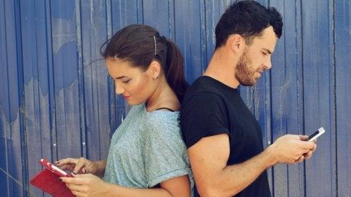Λάθη στη σχέση - Άνδρας και γυναίκα κοιτούν τα κινητά τους