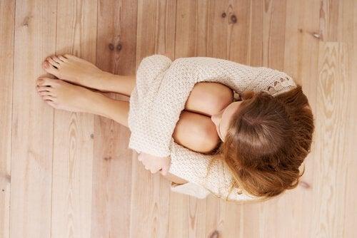 Γυναίκα φοβισμένη, κάθεται στο πάτωμα, οι εκμεταλλευτές χειραγωγούν