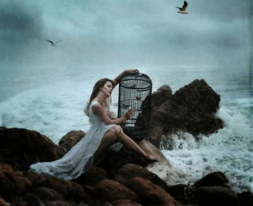 Γυναίκα με κλουβί πλάι στον ωκεανό