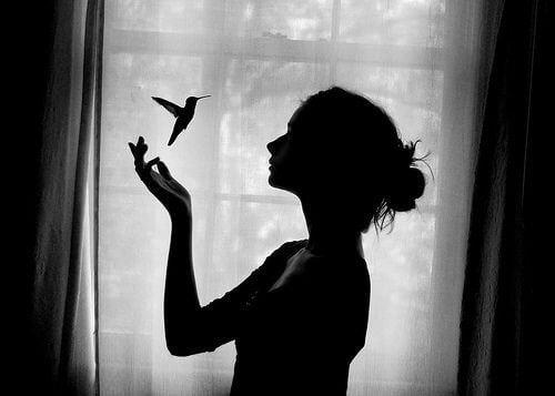 Γυναίκα με κολιμπρί μπροστά σε παράθυρο
