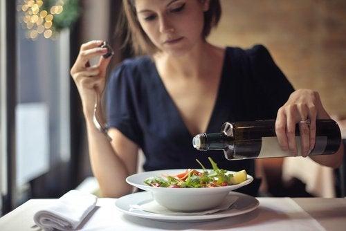 Γυναίκα βάζει λάδι σε σαλάτα