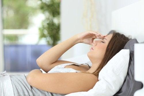 Γυναίκα με πονοκέφαλο ξαπλωμένη στο κρεβάτι- εντερικά προβλήματα