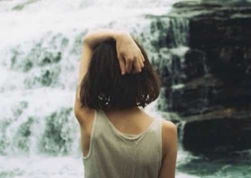 Σκεφτική γυναίκα μπροστά σε καταρράκτη