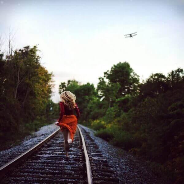 Γυναίκα τρέχει πάνω στις γραμμές του τρένου