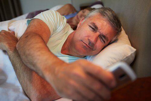 αποφύγετε την αύξηση βάρους: Άντρας με το κινητό στο κρεβάτι