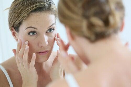 Γυναίκα κοιτά το πρόσωπό της στον καθρέφτη