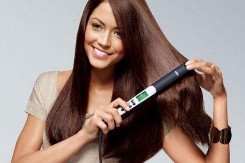Συμβουλές για να ισιώσετε τα μαλλιά σας - Γυναίκα χρησιμοποιεί σίδερο ισιώματος