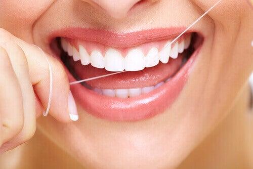 Έξυπνα κόλπα για να καταπολεμήσετε την κακή αναπνοή - Γυναίκα χρησιμοποιεί οδοντικό νήμα