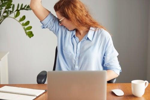 γυναίκα σε γραφειο με σηκωμένο χέρι- σημάδια που δίνουν οι μασχάλες σας