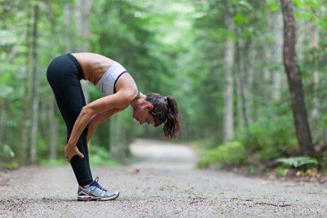 γυναίκα σε δάσος που κάνει ασκήσεις