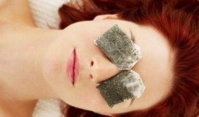 Πώς να καταπολεμήσετε την ξηροφθαλμία - Γυναίκα τοποθετεί σακουλάκια με χαμομήλι στα μάτια