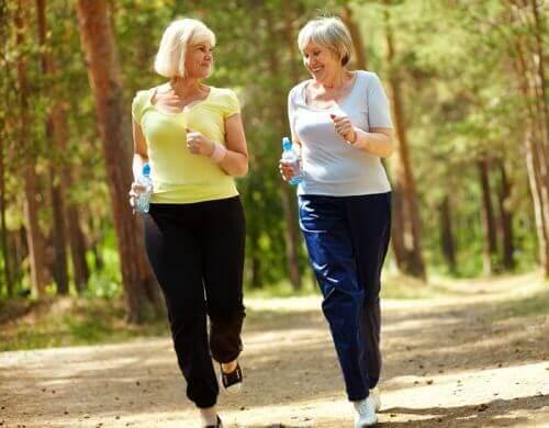 δύο γυναίκες με μπουκάλια νερό περπατάνε στο δάσος