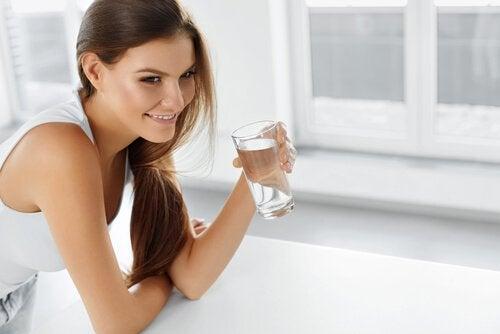 Συμπτώματα της κατακράτησης υγρών - Γυναίκα κρατά ποτήρι με νερό