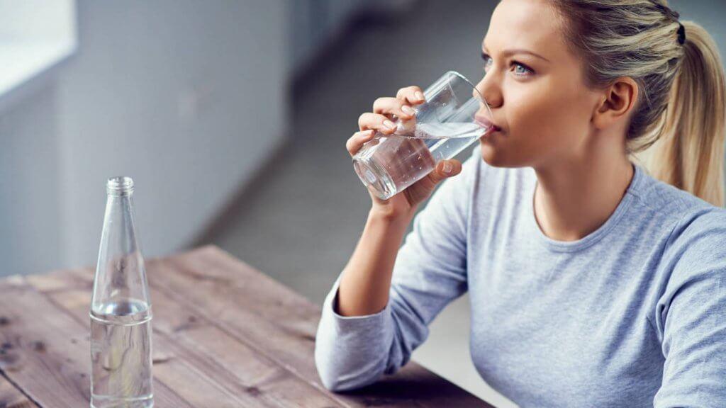 πόνο στα νεφρά γυναίκα που πίνει νερό