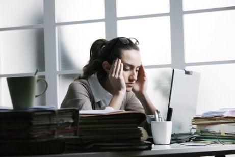γυναίκα με πονοκέφαλο σε γραφείο