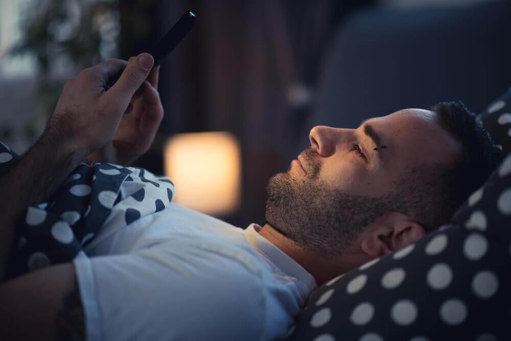 εθισμένοι στο κινητό άνδρας στο κρεβάτι με κινητό