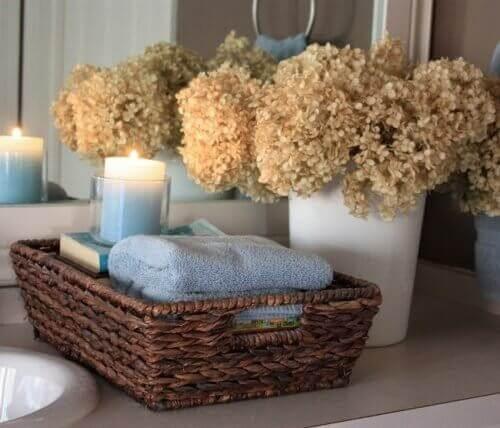 καλάθι μπάνιου με πετσέτες και κερί αναμμένο, διακόσμηση του μπάνιου