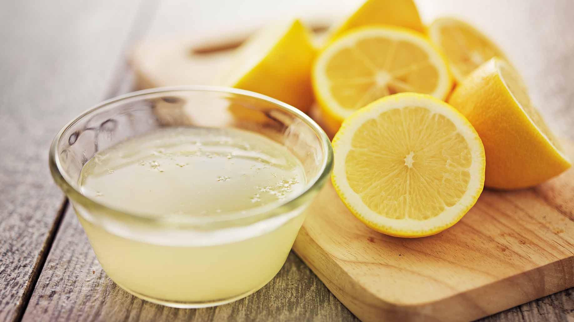 Χυμός λεμονιού σε μπολ και κομμένα λεμόνια