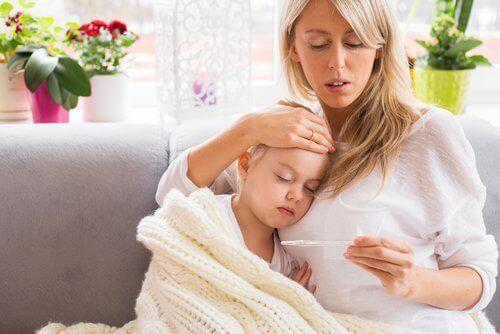 Συμπτώματα της μηνιγγίτιδας - Μητέρα παίρνει τη θερμοκρασία του παιδιού της