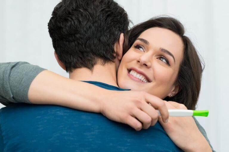 γυναίκα που αγκαλιάζει άνδρα με τεστ εγκυμοσύνης, ερωτήσεις που πρέπει να κάνετε στον/στην γυναικολόγο σας