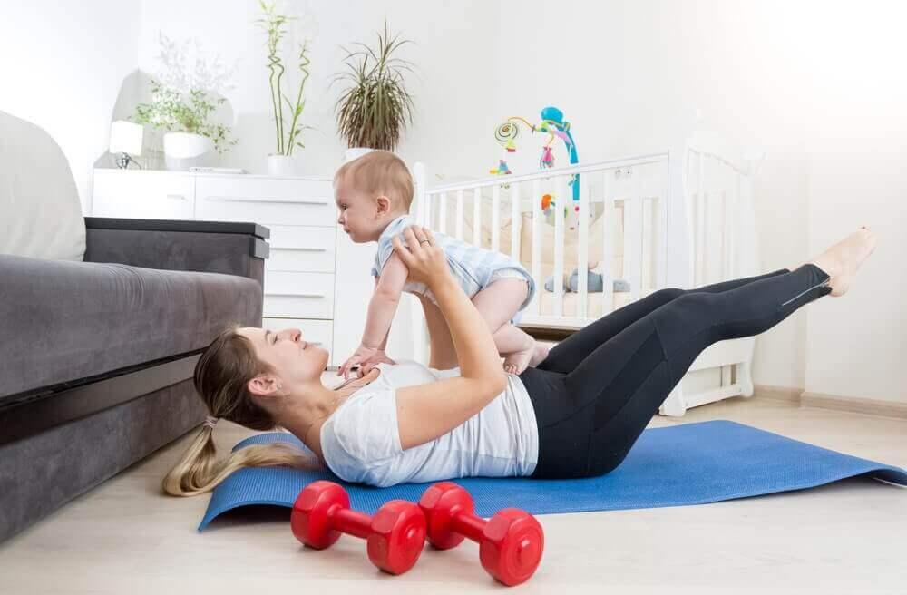 γυναίκα που έχει αγκαλια το μωρό της ξαπλωμένη στο πάτωμα