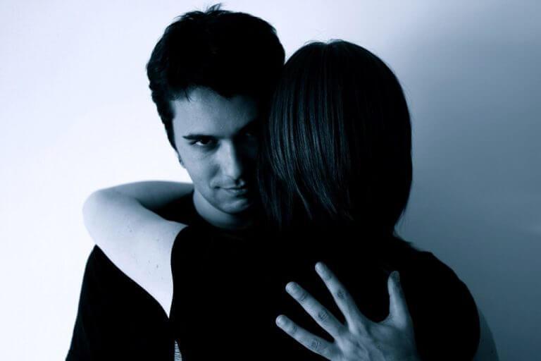 άνδρας που αγκαλιάζει μια γυναίκα, σχέση από φόβο ή ενοχή
