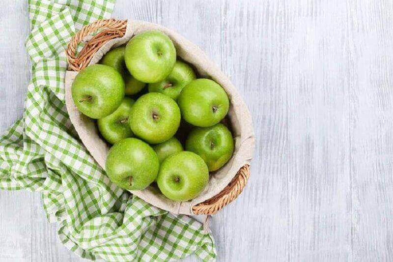 πράσινα μήλα σε καλάθι για να αποτοξινώσετε το σώμα