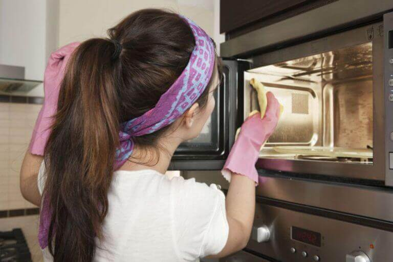Δυσάρεστες οσμές - Γυναίκα καθαρίζει φούρνο μικροκυμάτων