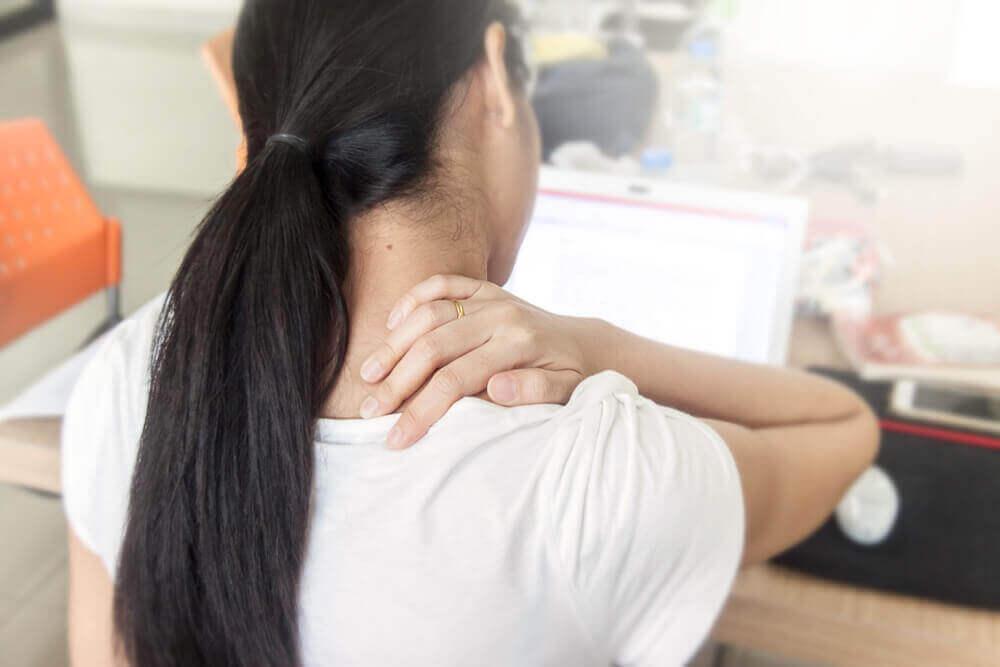 Πιθανές αιτίες για τον πόνο στην πλάτη - Γυναίκα πιάνει τον αυχένα της