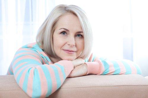 γυναίκα στην εμμηνόπαυση με τα χέρια στον καναπε