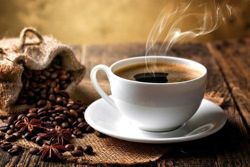 ζεστός καφές σε φλιτζάνι και κόκκοι καφέ