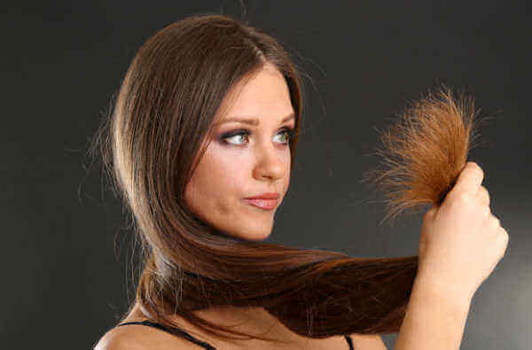 γυναίκα που κοιτάζει τις άκρες των μαλλιών μεταξένια μαλλιά