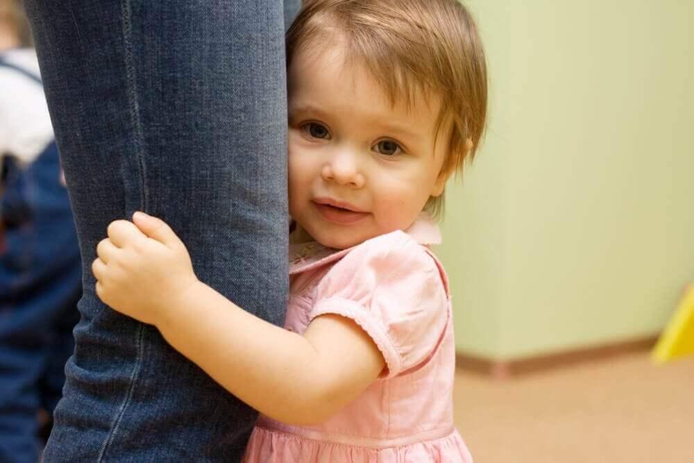 παιδί που αγκαλιάζει το πόδι του γονιού του