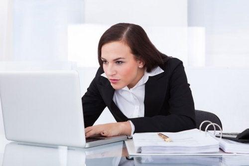 γυναίκα που γέρνει σε υπολογιστή- μεταβάλλεται η σπονδυλική στήλη λόγω άγχους