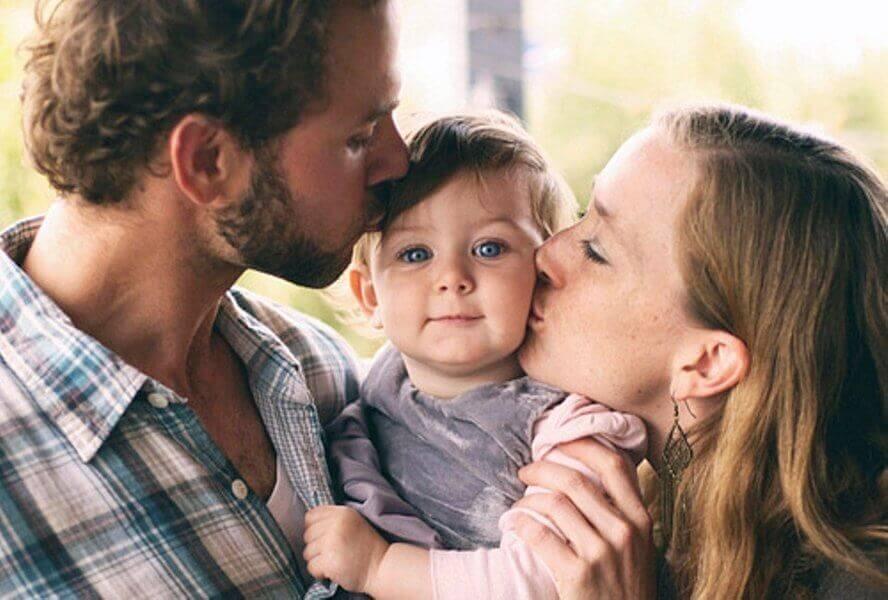 γονείς με παιδί αγκαλιά